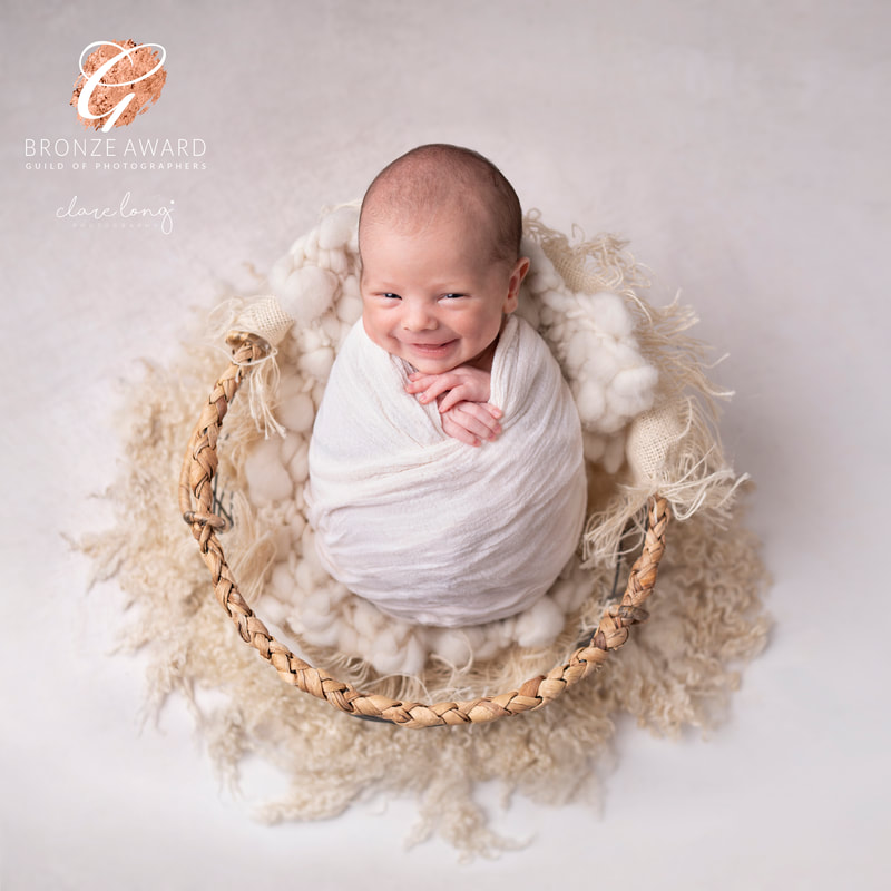 Newborn baby smiling swaddled kent baby photography