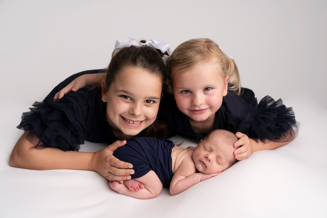 Big sister's proudly show their new baby brother in photography studio Bexley